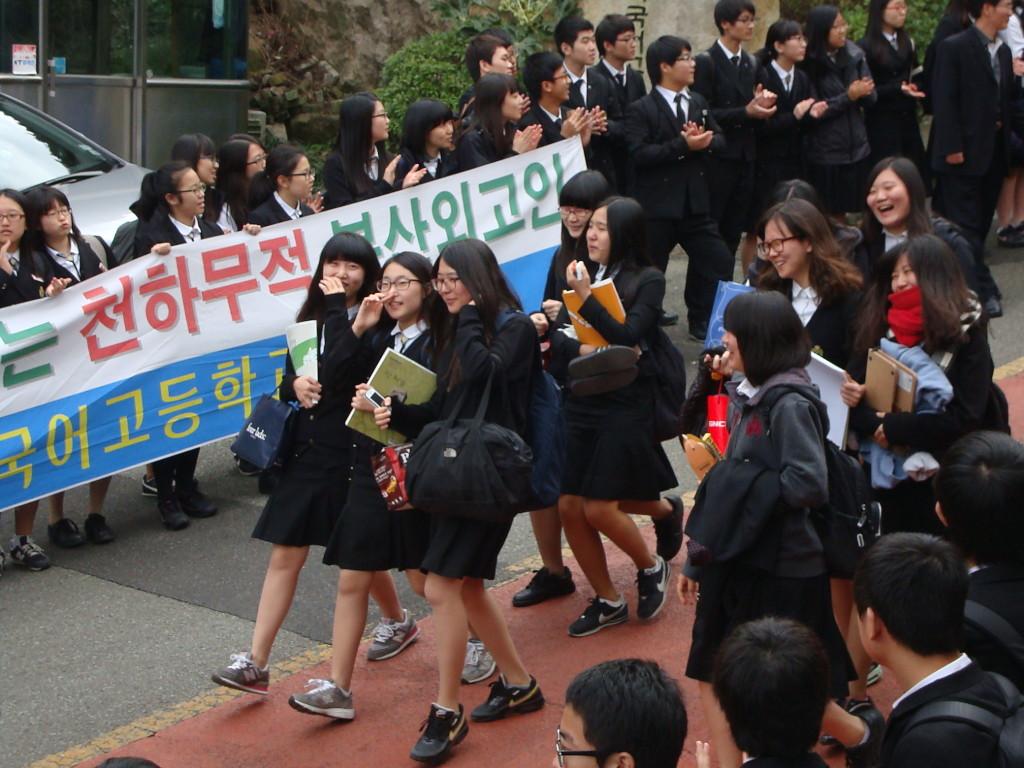 Para siswa kelas 3 yang akan menempuh ujian Suneung melalui barisan kehormatan dengan disemangati para adik kelas dan spanduk pemberi semangat.