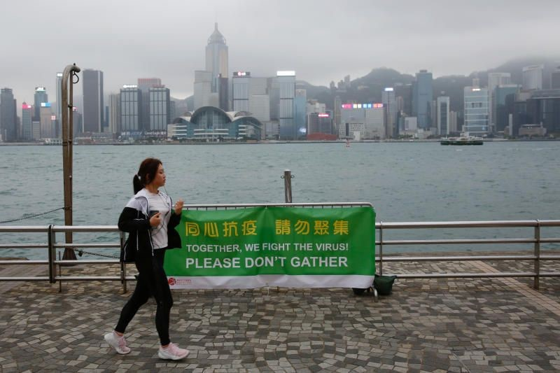 A woman running past a banner of health advice at Tsim Sha Tsui's tourist attraction, following the COVID-19 outbreak, in Hong Kong (Doc. Reuters).