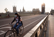 A cyclist wearing a face mask rides across a near-deserted Westminster Bridge in London, England, on April 8, 2020. (Photo by David Cliff/NurPhoto via Getty Images)