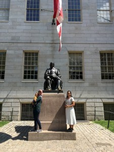 Dhini and her sister standing next to the John Harvard statue