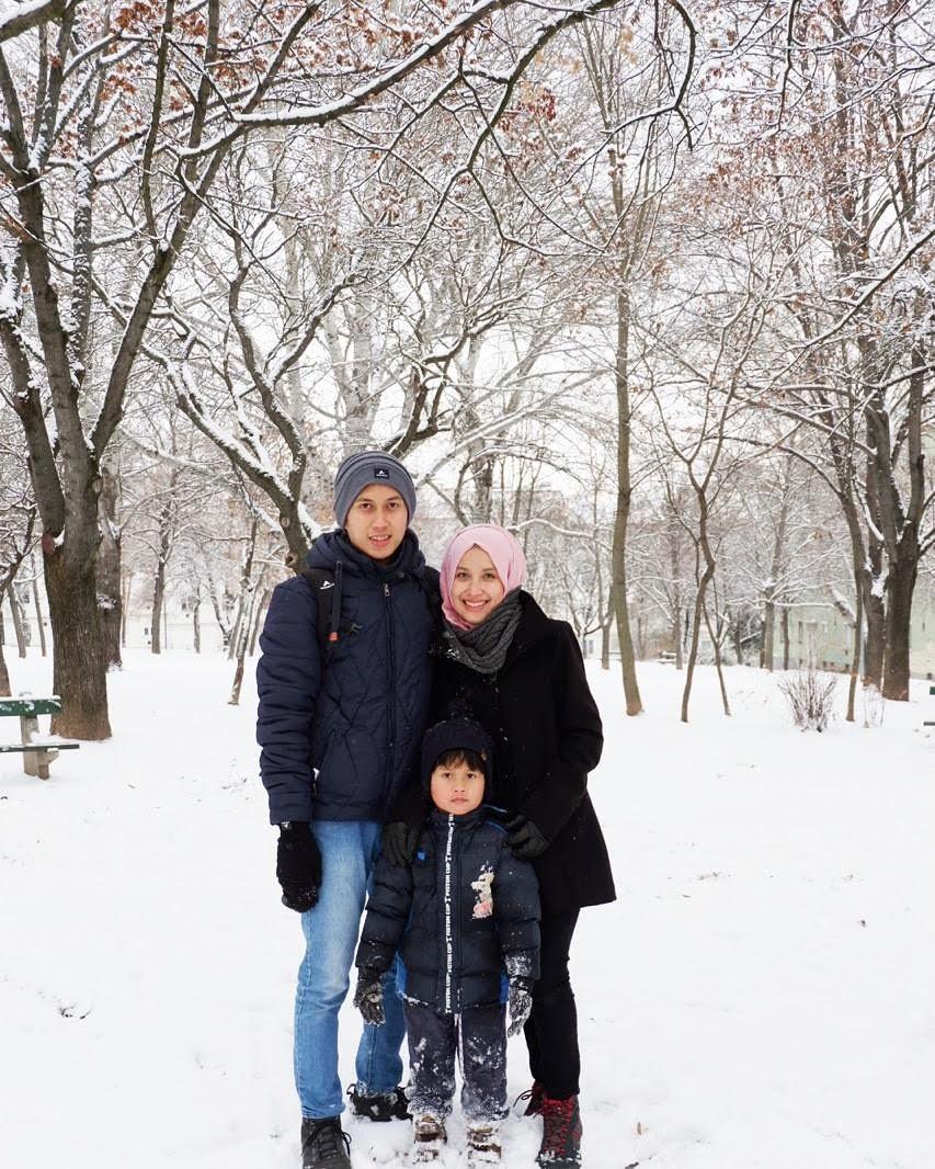 Fei (kiri) bersama istri dan anak menikmati musim dingin