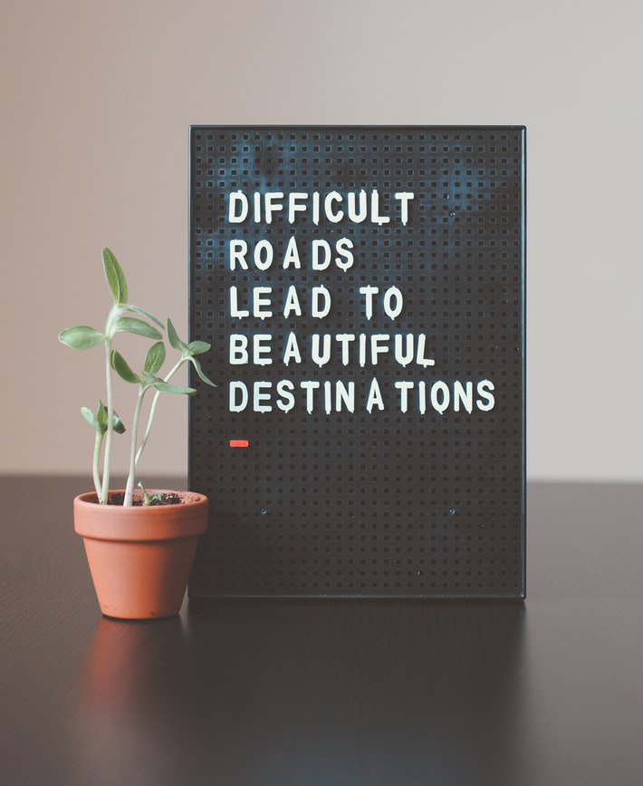 "A board on a table next to a pot of indoor plants. The board says ""difficult roads lead to beautiful destinations."""