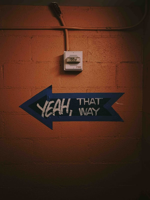 "An arrow on the wall with a spray-painted sentence that says ""Yeah, that way."""