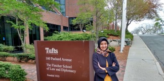 Dhini posing next to a sign at the Fletcher School
