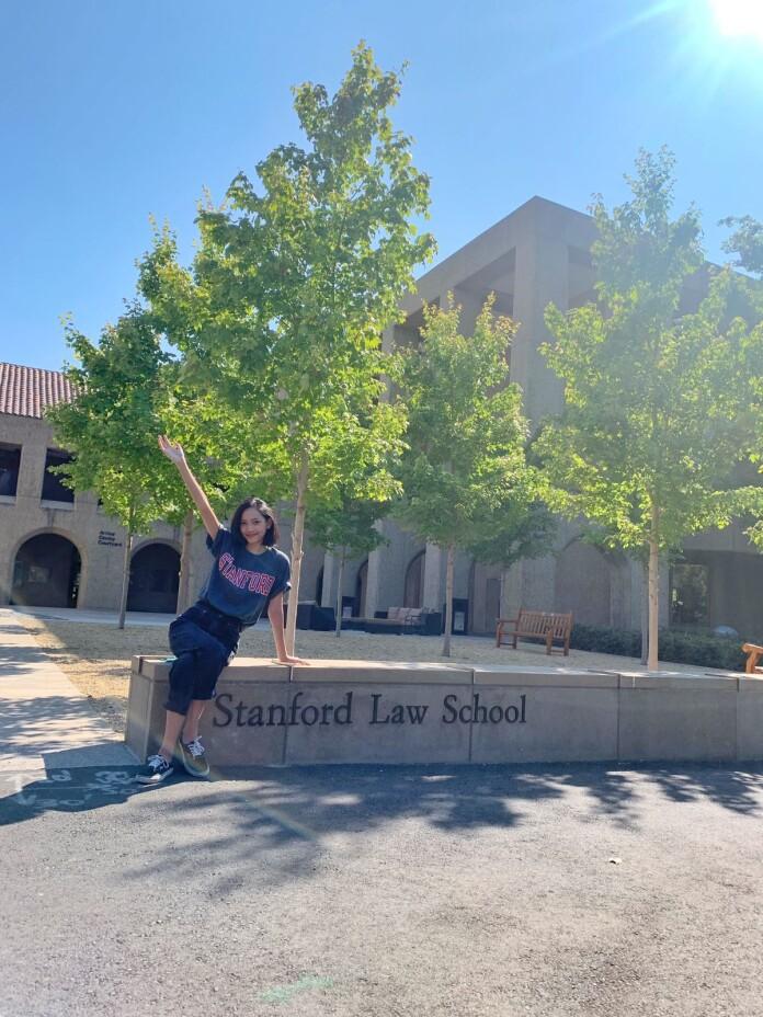 Nadira stood before Stanford Law School's signage.