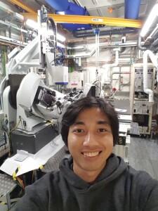 Penulis berfoto dengan latar belakang Difraktometer di I-19 X-ray Beamline, Synchrotron Diamond Light Source. Sumber: Penulis
