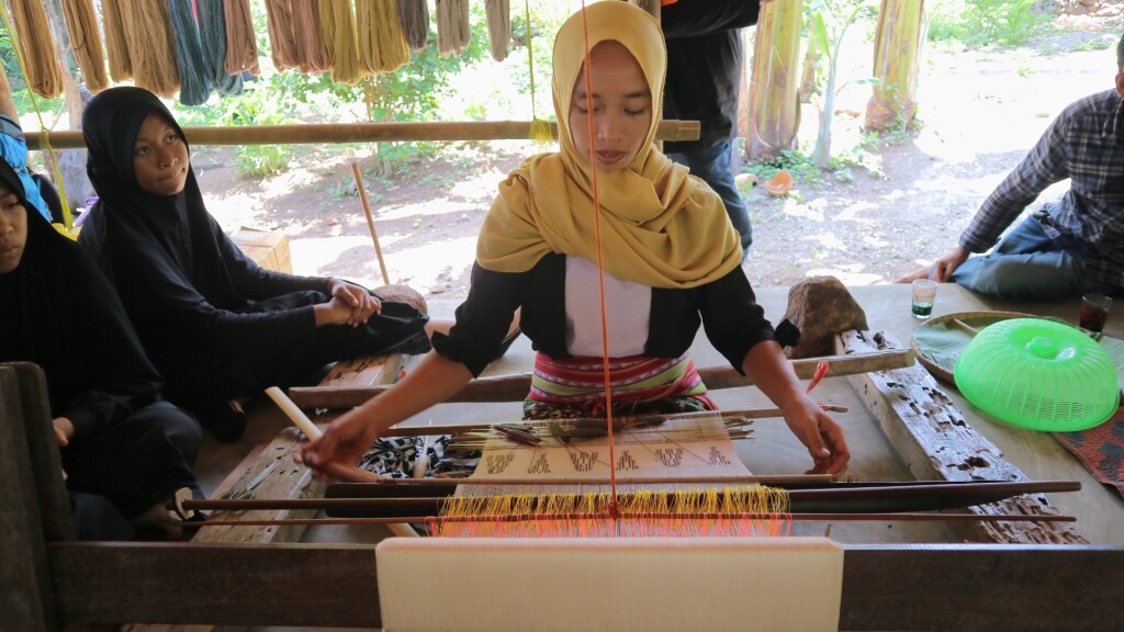 The project beneficiary demonstrating the hand-weaving process to local students. Source: TETE Bridging Future